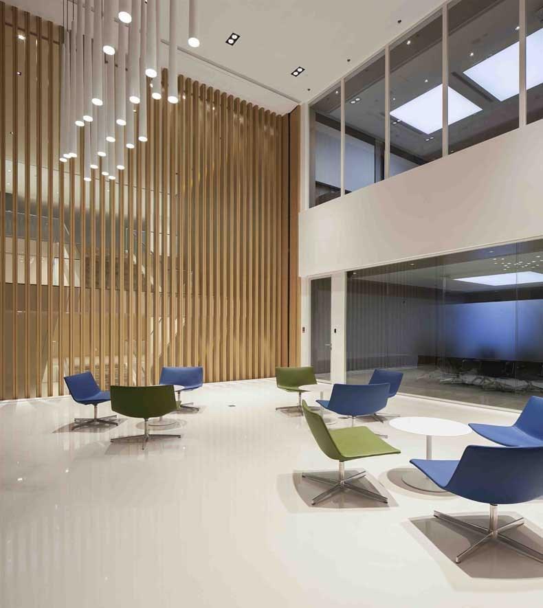 层高8米的垂直木色格栅logo墙壁配合两侧白色折纸